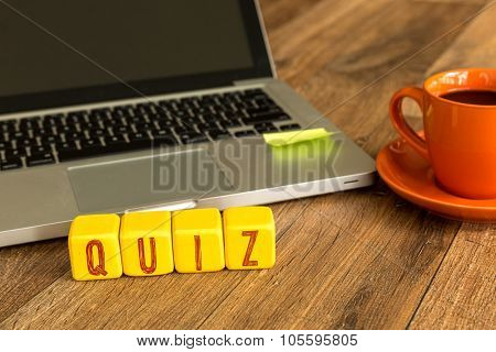Quiz written on a wooden cube in front of a laptop