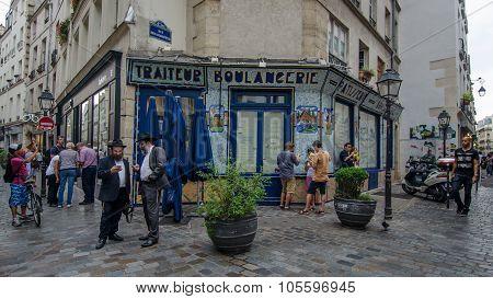 People gather on a street corner in Marais
