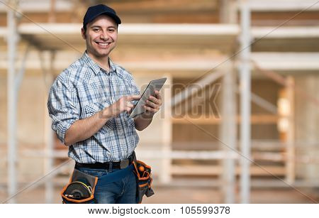 Artisan using his tablet computer in a construction site
