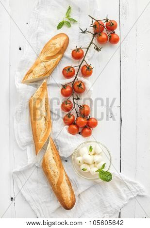 Baguette with banch of cherry-tomatoes, basil and mozzarella cheese on rustic white wooden backdrop,