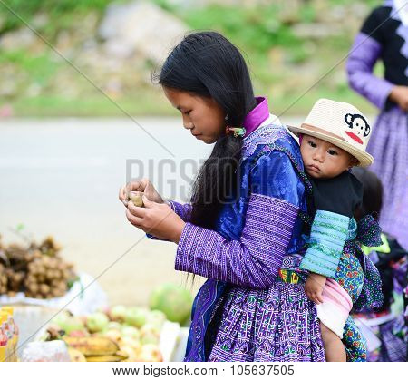 H'mong ethnic minority woman with her children in a festival in Mocchau, Vietna