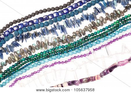 Bunch of natural semi-precious beads strands on white. poster
