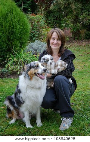 Dog Breeder With Australian Shepherd Adult Female Dog And Her Puppies In Arms