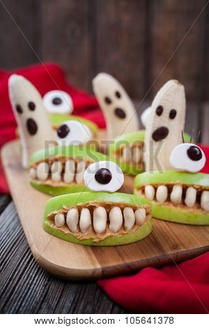 Spooky halloween edible monsters scary food healthy vegetarian snack dessert recipe for party decoration. Homemade cyclop apples with teeth and banana ghosts on dark vintage wooden background poster