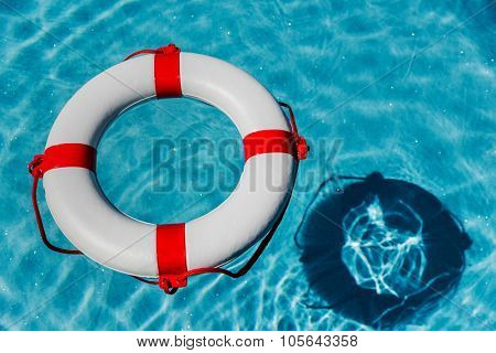 an emergency tire floating in a swimming pool. symbolic photo for rescue and crisis management in the financial crisis and banking crisis.