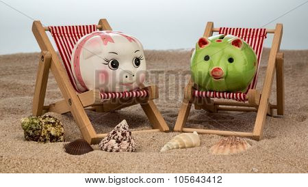 deckchair with piggy bank on the sandy beach. symbol photo for costs in travel, vacation, holiday. save on vacation
