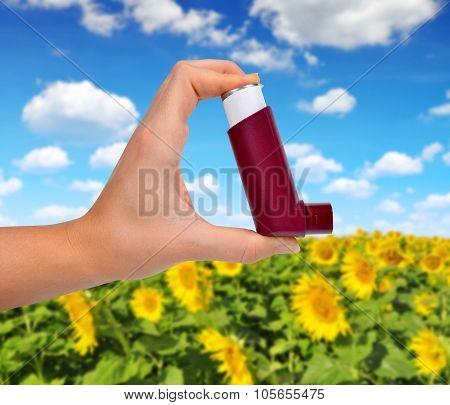 Asthma inhaler in hand.