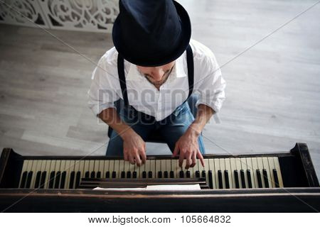 Handsome young man in hat making piano music, topside view