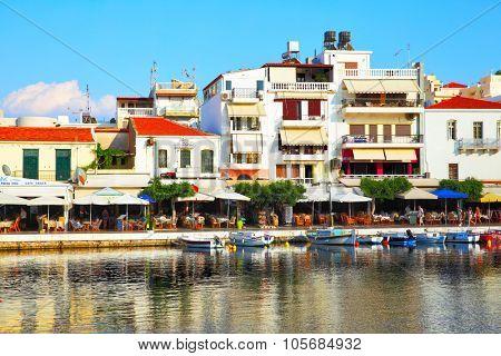 AGIOS NIKOLAOS, GREECE - JUNE 30, 2015: Picturesque waterfront of Voulismeni lake with boats, taverns and restaurantes in Agios Nikolaos, Crete Island