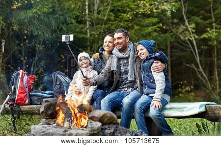 camping, travel, tourism, hike and people concept - happy family sitting on bench and taking picture with smartphone on selfie stick at campfire in woods poster