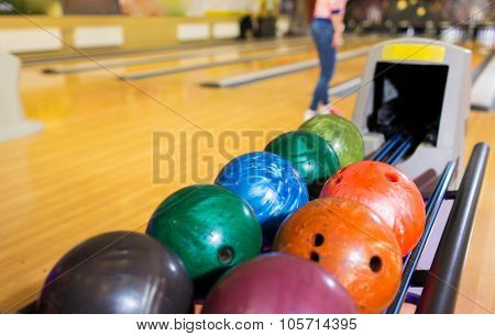 leisure, sport, technology and entertainment concept - close up of balls on ball return system in bowling club
