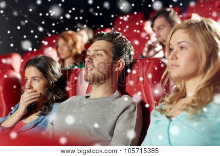 cinema, entertainment and people concept - friends watching horror, drama or thriller movie in theater over snowflakes
