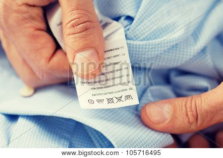 washing, clothes, housework and people - close up of male hands holding shirt and label with instructions