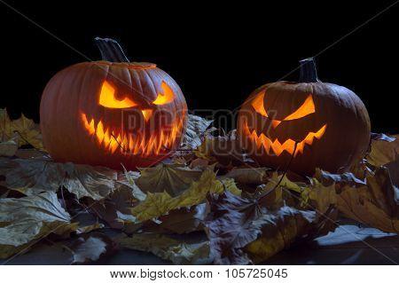 Spooky Pumpkins As Jack O Lantern Among Dried Leaves On Black