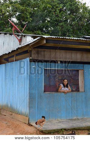 SAN FRANCISCO VILLAGE, PERU - OCTOBER 16, 2015: Woman in Window of Bodega. Small stores are staple in the Peruvian, Amazon region.