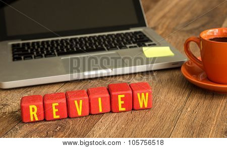 Review written on a wooden cube in front of a laptop