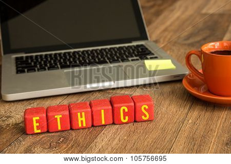Ethics written on a wooden cube in front of a laptop