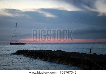 Fisherman And Yacht In Red Sunset