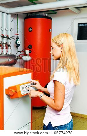 a young woman in the boiler room with heating. save energy