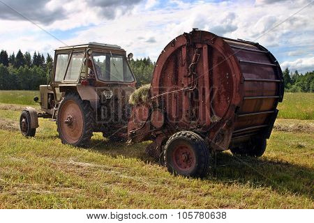 Haymaking Time, Round Baling Hay And Farming Tractor In Farmland.