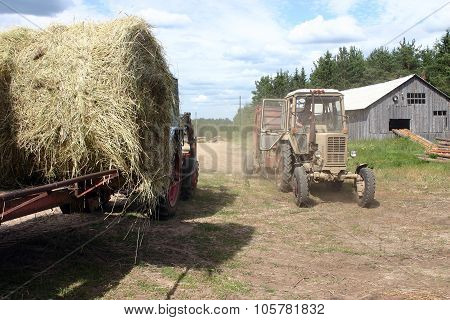 Russian Farm Tractor Moves Round Bales Of Hay Near Barn.