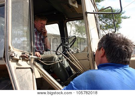 Villager Communicates With Cat-skinner, Who Sitting Tractor Cabin.