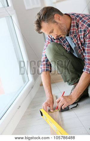 Man at home measuring wood plank for floor