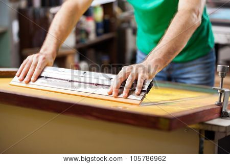 Midsection mid adult worker using squeegee in factory
