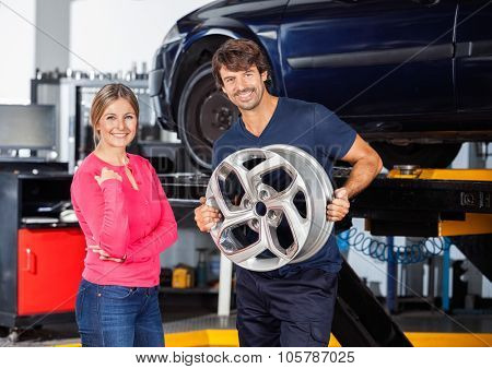 Portrait of happy mechanic holding alloy while standing with female customer at garage