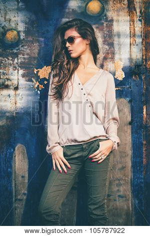 trendy fashion girl in silky beige shirt, green pants and sunglasses stand in front old rusty grunge metal door, outdoors