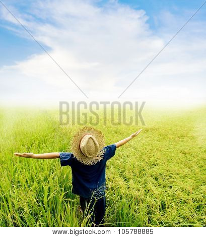 Golden color tone. Young Asian boy in thai traditional blue shirt and straw hat feeling relax on the rice field be fore harvesting on blue sky white cloud and fog in the morning. poster