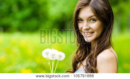 Portrait of young beautiful woman hands dandelions in the park. Concept of youth and natural beauty