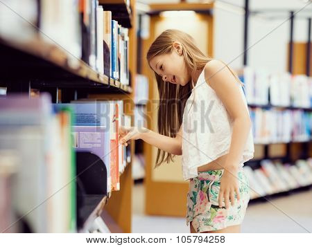 Little girl picking a book in public library