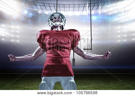 Aggressive American football player in red jersey screaming against american football arena