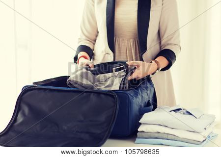 business, trip, luggage and people concept - close up of woman formal male clothes into travel bag at home