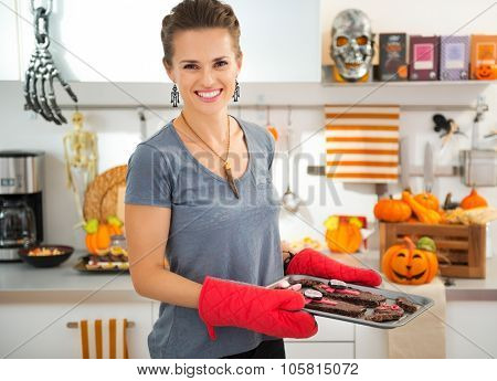 Smiling modern housewife in decorated kitchen holding tray with freshly baked Halloween biscuits for Trick or Treat. Ready to halloween party. Traditional autumn holiday poster