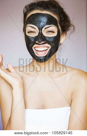 Young beautiful woman with a mask for the face of the therapeutic black mud poster