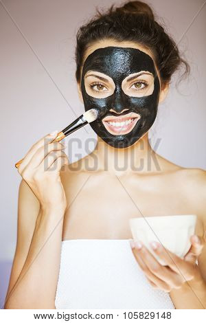 Young Beautiful Woman Applying A Mask For The Face Of The Therapeutic Black Mud