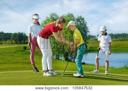 Trainer works with children at golf school