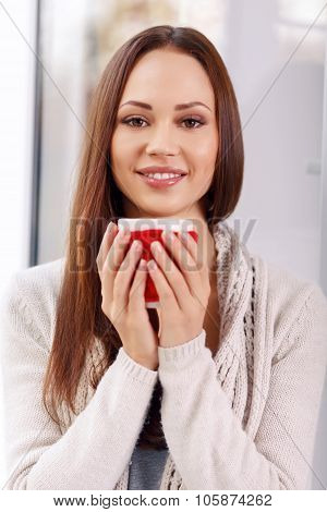 Attractive young lady with a cup of drink.