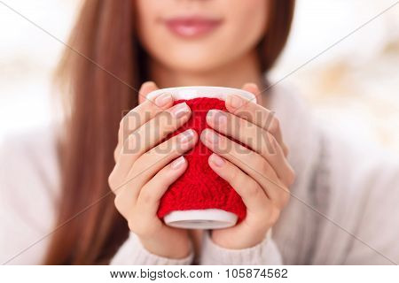 Girl holds the cup in cute cupholder.