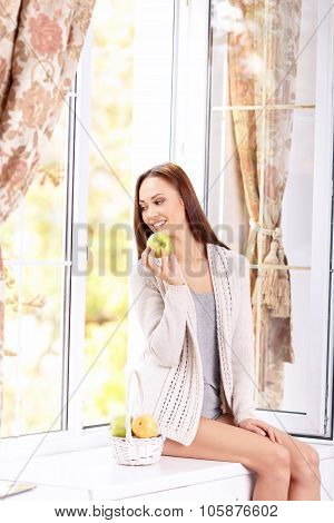 Young lady on the windowsill with seasonal fruits.