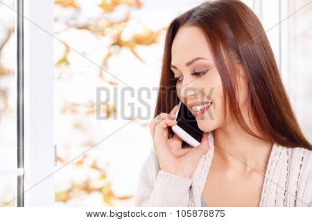 Lovely young lady is speaking on the phone.