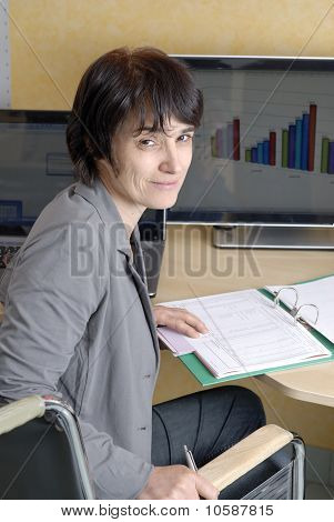 Disabled Business Woman In Wheelchair At Her Desk