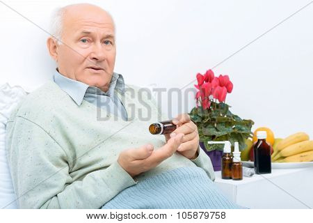 These are medicines. Elderly man sits on his bed and holds pills vial while there are other remedies on the background. poster