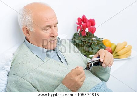 Senior aged man pours himself cough syrup.