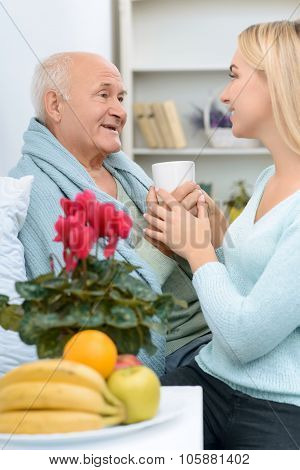 Smiling senior aged man receives a cup of tea.