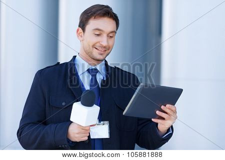 Newshawk is amused by information on his tablet.