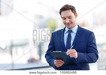 Gentleman in suit using a clipboard.