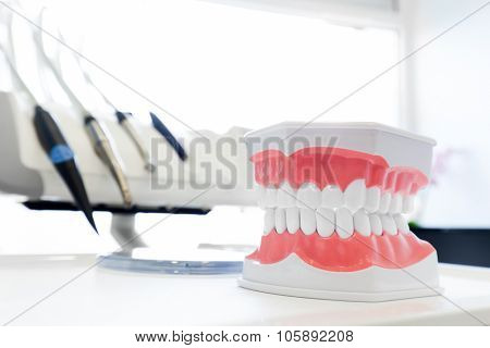 Clean teeth denture, dental jaw model in dentist's office. Dentistry instruments and equipment in the background